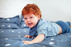 Happy redhead toddler baby having fun in bed stock image