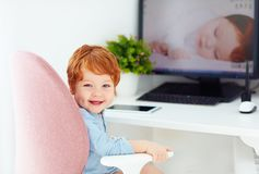 Happy redhead toddler baby boy is sitting in office chair at working place stock image