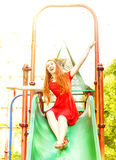Happy redhead woman on a children slide Stock Image