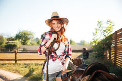 Happy redhead woman cowgirl preparing saddle for riding horse Stock Photography