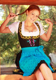 Happy Redhead Woman in Dirndl. Beautiful smiling redhead woman wearing a dirndl dress. She is sitting in a window pulling on her pigtails Stock Images