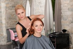 Happy redhead woman getting new haircut. Royalty Free Stock Photography