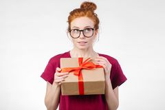 Happy redhead woman in glasses holding gift box on white background royalty free stock image