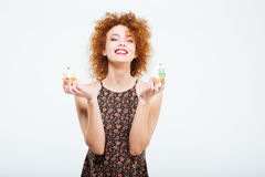 Happy redhead woman holding cakes Stock Image