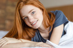 Happy redhead woman lying in the bed Royalty Free Stock Photo