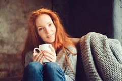 Happy Redhead Woman Relaxing At Home In Cozy Winter Or Autumn Weekend With Book And Cup Of Hot Tea, Sitting In Soft Chair Stock Image