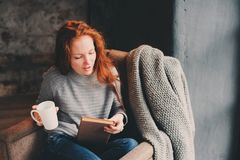 Happy redhead woman relaxing at home in cozy winter or autumn weekend with book and cup of hot tea, sitting in soft chair. With blanket stock photography