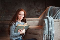 Happy redhead woman relaxing at home in cozy winter or autumn weekend with book and cup of hot tea, sitting in soft chair Stock Photo