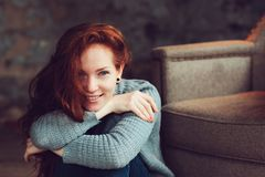 Happy redhead woman relaxing at home in cozy winter or autumn weekend with book and cup of hot tea, sitting in soft chair royalty free stock image