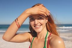 Happy redhead woman standing on the beach. Portrait of happy redhead Caucasian woman standing on the beach royalty free stock photos