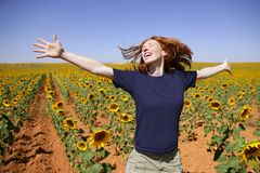 Happy redhead woman in sunflowers field Royalty Free Stock Photo
