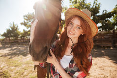 Happy redhead young woman cowgirl with her horse in village Royalty Free Stock Image