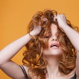 Happy redheaded young woman with luxurious curly hair. Studio portrait on yellow background. Excellent hair. Happy redheaded young woman with luxurious curly Stock Image