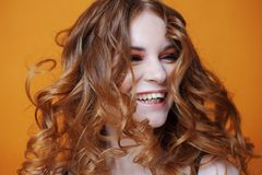 Happy redheaded young woman with luxurious curly hair. Studio portrait on yellow background. Excellent hair. Happy redheaded young woman with luxurious curly Royalty Free Stock Images