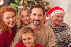 Happy relatives enjoying celebration of New Year. Joyful married couple and their children are celebrating Christmas with grandfather. They are sitting and Royalty Free Stock Photo