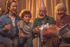 Cheerful family celebrating birthday of son. Happy relatives giving present to cheerful curly boy. They sitting on sofa. Fun concept Royalty Free Stock Photography