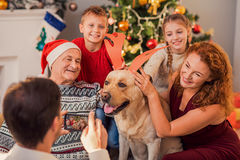 Happy relatives having fun with pet on holiday. Father is photographing his family playing with dog. They are sitting near Christmas tree and laughing. Woman is royalty free stock photography