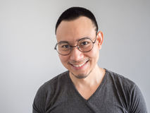Happy and relax freelance man. Happy Asian freelance man with skinhead and relaxing mile haircut royalty free stock image