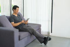 Happy relax man using mobile phone sitting on comfortable sofa n. Ear window at home,Digital lifestyle Royalty Free Stock Photos
