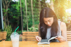 Happy relax times with reading book, Asian women Thai teen smile with book in garden Stock Images