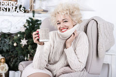 Happy relaxed beautiful stylish blonde woman is sitting in a comfortable chair beige knitted. Stock Image