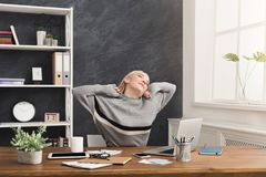 Young relaxed business woman in office. Happy relaxed business woman in office. Young girl having rest at workplace, stretching, dreaming about something, copy Stock Image