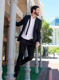 Happy relaxed businessman holding on to pole outside Royalty Free Stock Photos