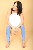 Happy Relaxed Cheerful Attractive Young Woman Sitting on a White Chair Royalty Free Stock Image