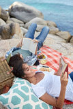 Happy and relaxed couple reading during a picnic on the rocks, n Stock Image