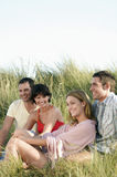 Happy And Relaxed Couples Sitting In Grass stock photo