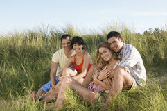 Happy And Relaxed Couples Sitting In Grass Royalty Free Stock Photo