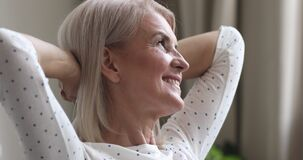 Happy dreamy older woman relax hands behind head at home