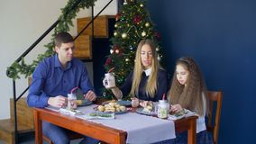 Happy family having christmas dinner at home. Happy relaxed family and cute elemenatry age daughter having christmas dinner, eating cookies , drinking hot stock footage