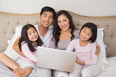Happy relaxed family of four using laptop in bed. Portrait of a happy relaxed family of four using laptop in bed at home Royalty Free Stock Images