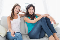 Happy relaxed female friends sitting in living room Royalty Free Stock Photography