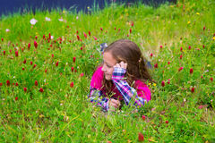 Happy relaxed kid girl on a spring flowers meadow Stock Photo
