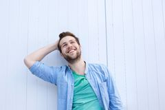 Happy relaxed man smiling with hand in hair stock photography