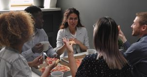 Happy relaxed multiracial business team people laughing eating takeaway pizza