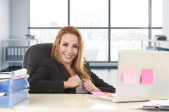 Bossy business woman with blond hair smiling confident leaning on office chair working at laptop computer. Happy and relaxed 40s bossy business woman with blond Royalty Free Stock Photo
