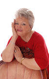 Happy relaxed senior woman. A happy smiling senior woman leaning over a armchair with one hand Royalty Free Stock Images