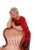 Happy relaxed senior woman. A happy smiling senior woman leaning over a armchair with one hand Royalty Free Stock Photo
