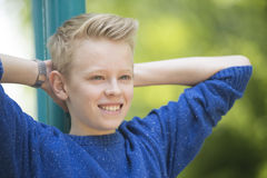 Happy relaxed smiling teenager boy outdoor. Portrait happy smiling blond teenage boy outdoor, relaxed and positive with arms up behind head, blurred background Royalty Free Stock Photo