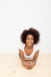 Happy relaxed woman lying on a wooden floor Stock Image