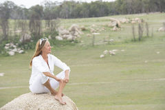 Happy relaxed woman outdoor sitting on rock Royalty Free Stock Images
