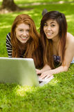 Happy relaxed women using laptop in park Stock Photos