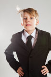 Happy relaxed young boy in black suit. Studio portrait of smiling and relaxed young boy in black suit with wind blowing hair Royalty Free Stock Photos