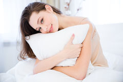 Happy relaxed young woman hugging pillow on bed Royalty Free Stock Photos