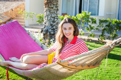 Happy relaxed young woman lying on hammock in casual summer dress.  Royalty Free Stock Image