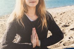 Happy relaxed young woman meditating in a yoga pose at the beach royalty free stock photo