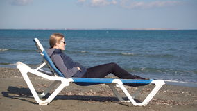 Happy relaxing woman on chaise-longue at perfect wild sandy beach with blue sea view during off-season. On Cyprus stock footage